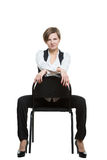 Woman sits astride a chair. sexy shows wrist. Dominant position. Isolated on white background Stock Images