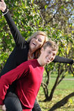 Woman sits on back of man and her arms spread out to sides Royalty Free Stock Images