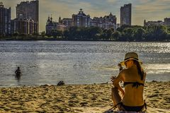 A woman sits on the beach. A woman with the hat on sits on the beach of Dnipro river in Kyiv city stock photos