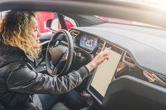 Woman sits behind wheel in car and uses electronic dashboard. Girl traveler looking for way through navigation system. Young woman sits behind wheel in car and royalty free stock image