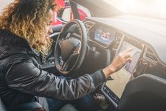 Woman sits behind wheel in car and uses electronic dashboard. Girl traveler looking for way through navigation system. Young woman sits behind wheel in car and royalty free stock photos