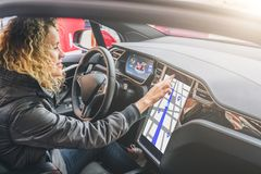 Woman sits behind wheel in car and uses electronic dashboard. Girl traveler looking for way through navigation system. Young woman sits behind wheel in car and stock photography
