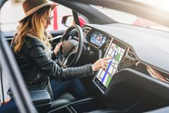 Woman sits behind wheel in car and uses electronic dashboard. Girl traveler looking for way through navigation system. royalty free stock photo