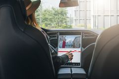Woman sits behind wheel in car and uses electronic dashboard. Girl traveler looking for way through navigation system. royalty free stock photography