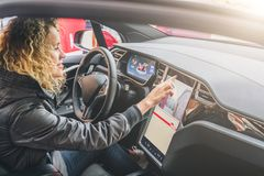 Woman sits behind wheel in car and uses electronic dashboard. Girl traveler looking for way through navigation system. Young woman sits behind wheel in car and stock images