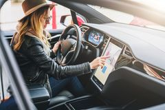 Woman sits behind wheel in car and uses electronic dashboard. Girl traveler looking for way through navigation system. stock image
