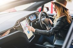 Woman sits behind wheel in car and uses electronic dashboard. Girl traveler looking for way through navigation system. Young woman sits behind wheel in car and Stock Photos
