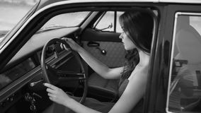 A woman sits behind the wheel of a vehicle is similar to a retro movie character. A young and beautiful woman who sits behind the wheel of a vehicle looks like a stock video footage