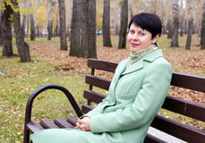 Woman sits on a bench in autumn park Royalty Free Stock Photos