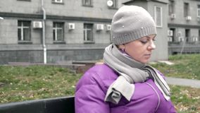 A woman sits on a bench with a book stock footage
