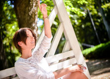 Woman Sits on Bench Calling Someone From Distance Royalty Free Stock Image