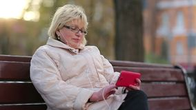 Woman sits on the bench near the road and uses red cell phone stock footage