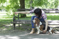 Woman sits on a bench in the park with his beautiful dog and sho Royalty Free Stock Images