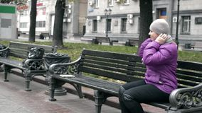 A woman sits on a bench in the Park stock video footage