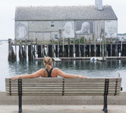 Woman sits on a bench in Provincetown Harbor Royalty Free Stock Photo