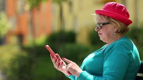 Woman sits on the bench and uses red cell phone. Senior woman in red hat sits on the bench and uses red smartphone. Woman looking and flipping through the photos stock video footage