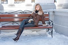 Woman sits on a bench in a winter park Stock Photography