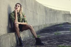 Woman Sits Besides Gray Concrete Wall Stock Photography