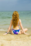 Woman sits in bikini by the sea. And has a rest stock photo
