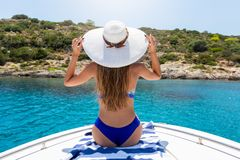 Woman sits on a boat and enjoys the view to the Mediterranean sea stock photo