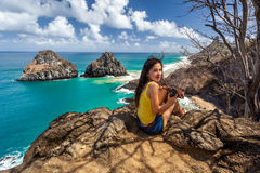 Woman sits with camera near Two brother Rock ,Fernando de Noronha Royalty Free Stock Photography