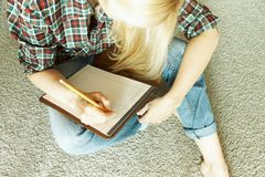 The woman sits on the carpet and writes stock images