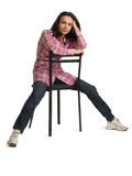 Woman sits on a chair back to front. Young woman in pink jacket sits on a chair back to front Royalty Free Stock Photos
