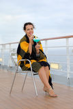Woman sits on chair and holds cocktail. Woman wrapped in plaid sits on chair on cruise liner deck and holds cocktail Stock Image