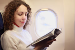 Woman sits in chair nea illuminator of airplane royalty free stock photos