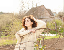 Woman sits on a chair in a spring garden Stock Photo