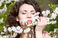 Woman sits on a chair in a spring garden Stock Image