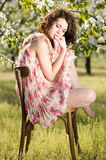 Woman sits on a chair in a spring garden Royalty Free Stock Photo