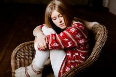 Woman sits in a chair wearing a sweater with the r Royalty Free Stock Image