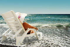 Woman sits in chaise lounge on the sea beach. Young lady in hat sits in chaise lounge on the sea beach stock photography
