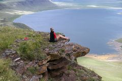 A woman sits on a cliff above the lake. stock images