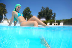 Woman sits in day-time in pool. Woman in swimming suit sits in day-time in pool and put leg into water Stock Photos