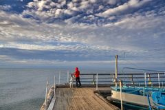 Woman walk with dog on wooden sea pier. Woman sits with dog on wooden sea pier at sunny windy day stock photography
