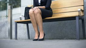 Woman sits down on bench, tired of walking in uncomfortable high-heeled shoes stock video