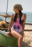 A woman sits on the edge of a boat wearing sunglasses and a hat. On the beach Stock Photography