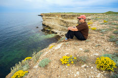 Woman sits on  edge of the cliff in  black sea . Stock Photo