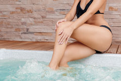 Woman sits on the edge of a Jacuzzi Royalty Free Stock Image