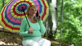 Woman sits on a fallen tree in the forest and communicates via smartphone stock video footage