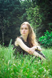 Woman sits at a forest's meadow Stock Images