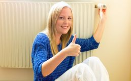 Woman sits in front of radiators Stock Image