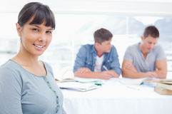 A woman sits in front of to men as she looks at the camera Stock Photography