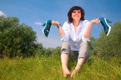 Woman sits on grass and holds shoes in hands Royalty Free Stock Photos