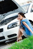 Woman sits on the grass near her broken cabriolet Stock Photos