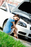 Woman sits on the grass near her broken car Royalty Free Stock Photography