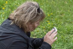 A woman sits on a green grass and looks into the smartphone, rear and side view royalty free stock photo