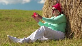 Woman sits on green grass near haystack and makes photos on his smartphone stock video